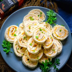 Ham and Cheese Pinwheels are easy to make appetizer. This cold party appetizer is made using tortilla wraps, cream cheese, and hot sauce. Here is how to make it.