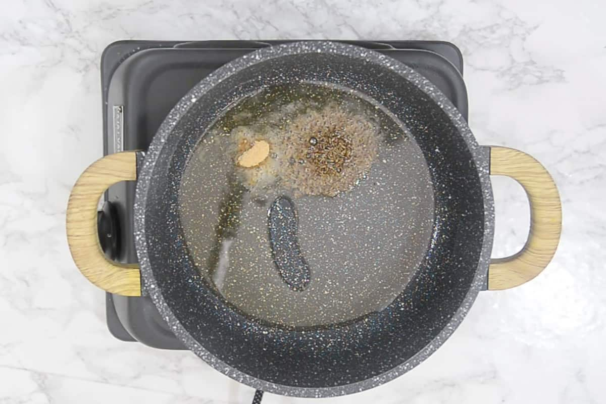 Cumin seeds and hing added in the pan.