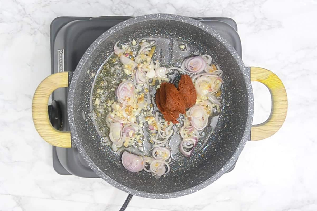 Thai red curry paste added to the pan