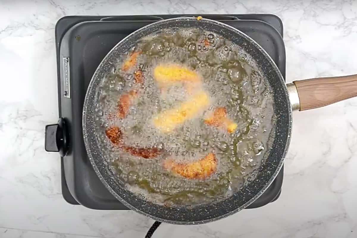 Fish fingers frying in hot oil.