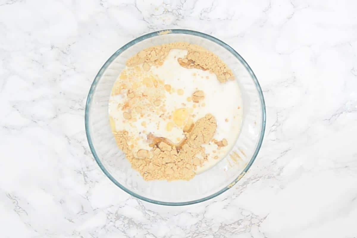 Biscuit powder, ENO Fruit salt, vanilla extract, oil and milk added in a bowl.