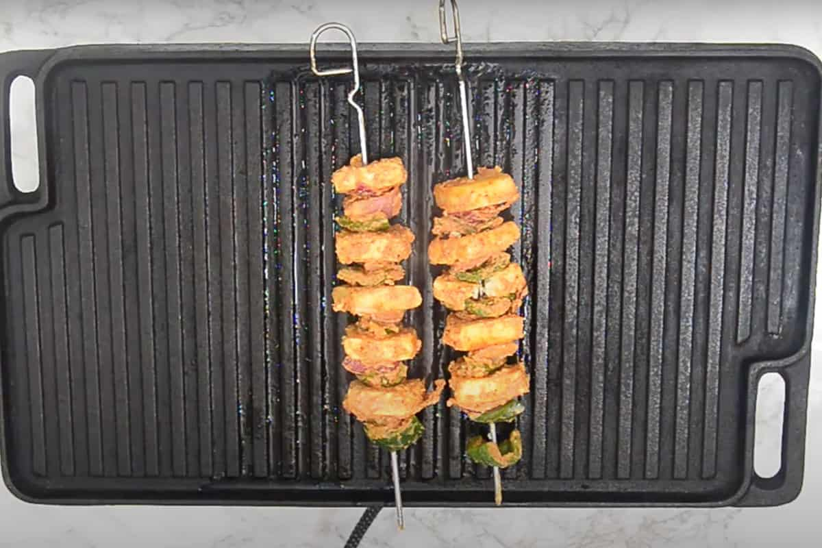 Paneer, capsicum and onion threaded on metal skewers and grilling on a grill pan.