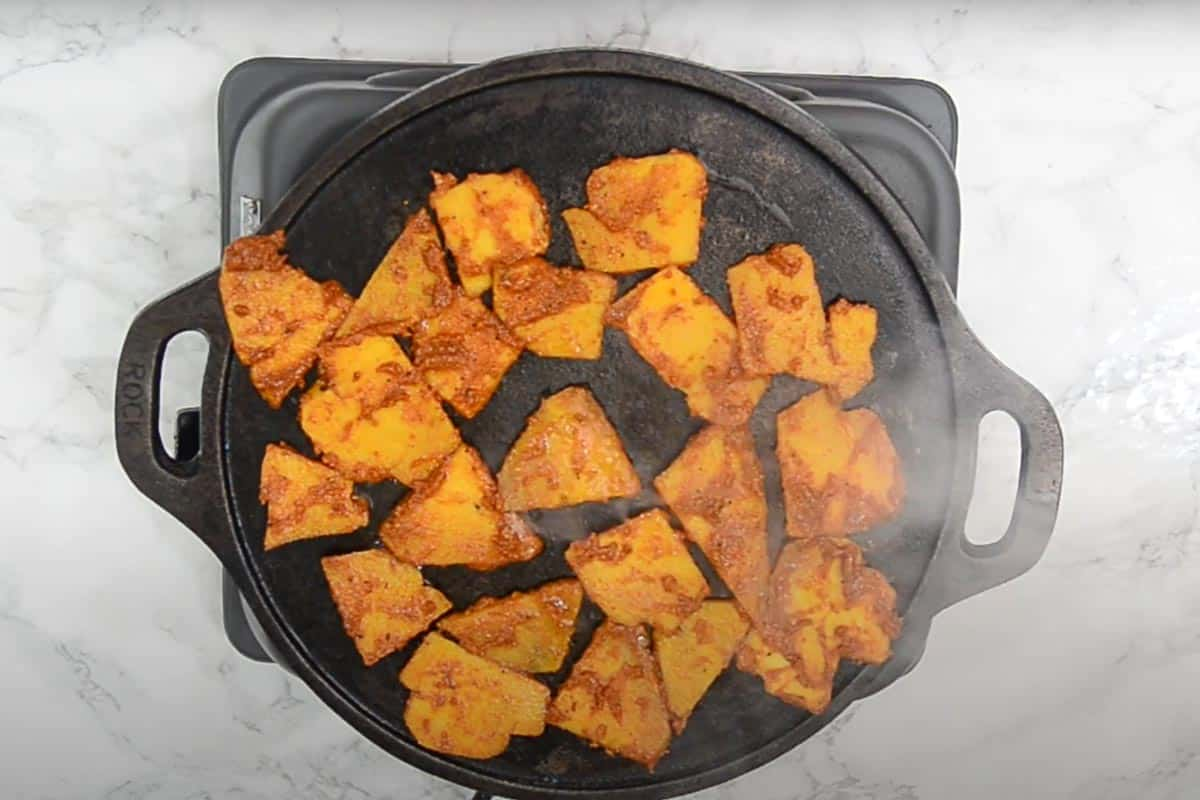 Yam slices frying in a pan.