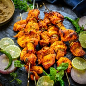 This tandoori chicken tikka or murgh tikka is a popular North Indian starter, where marinated chicken is grilled until perfection. This authentic snack recipe is great to make for parties or get-togethers.