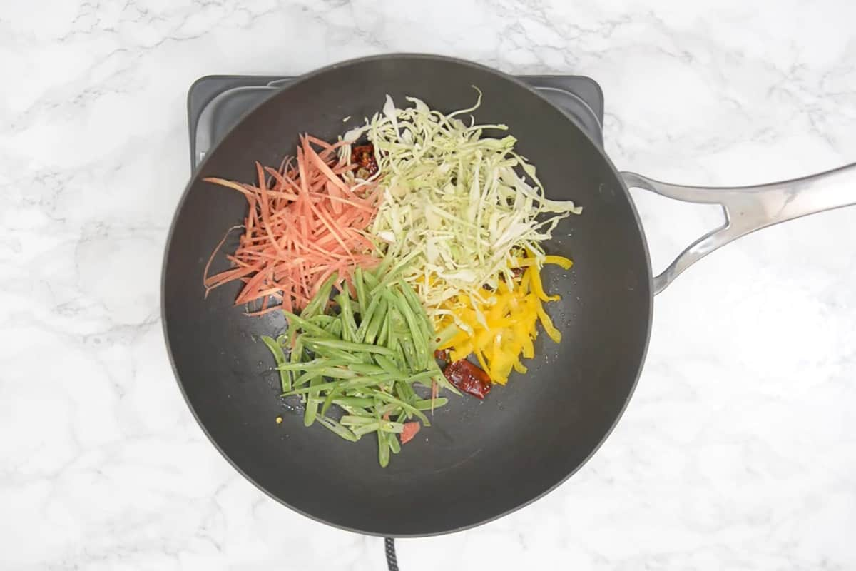 Yellow bell pepper, carrot, beans and cabbage added in the pan.