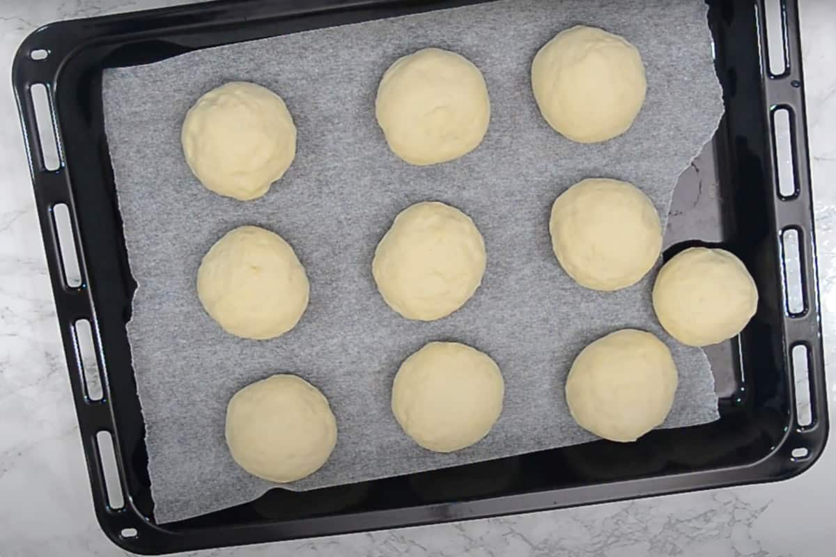 Balls arranged on a baking tray lined with parchment.