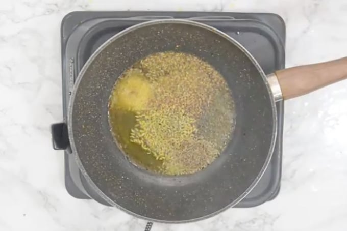 Mustard seeds, cumin seeds, hing, fennel seeds and carom seeds added in oil.