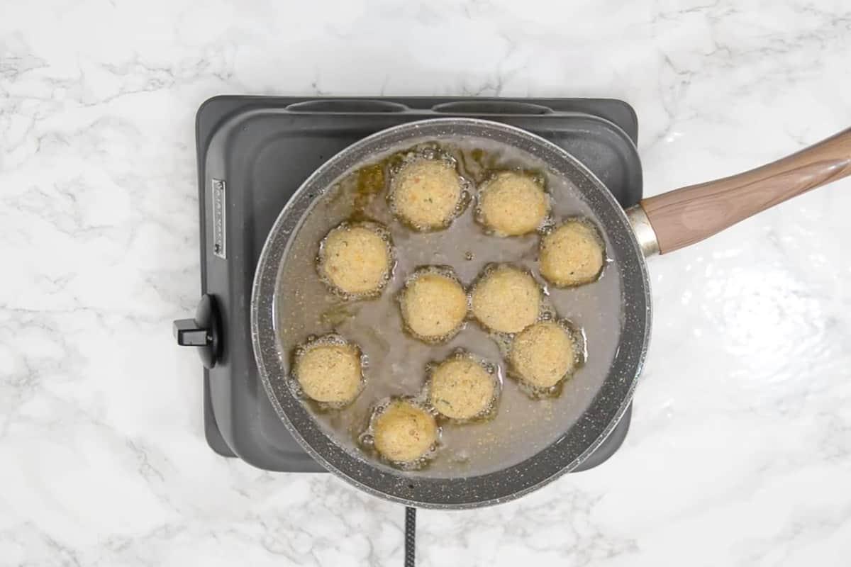 Balls frying in hot oil.