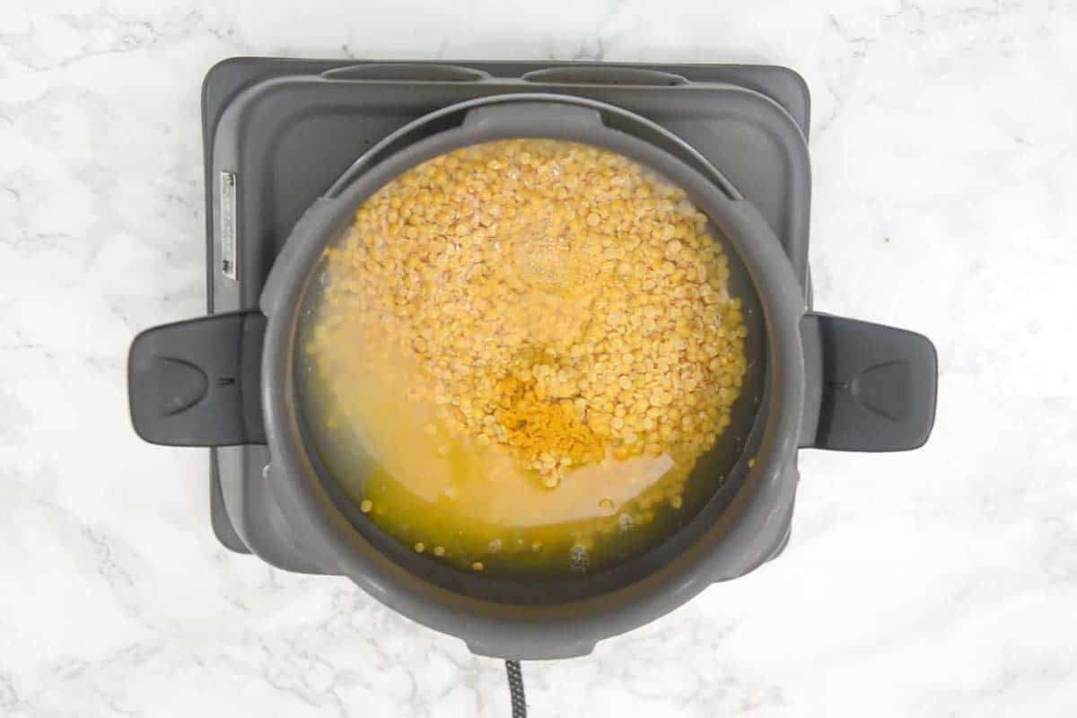 Dal, salt, turmeric powder and water added in a pressure cooker.