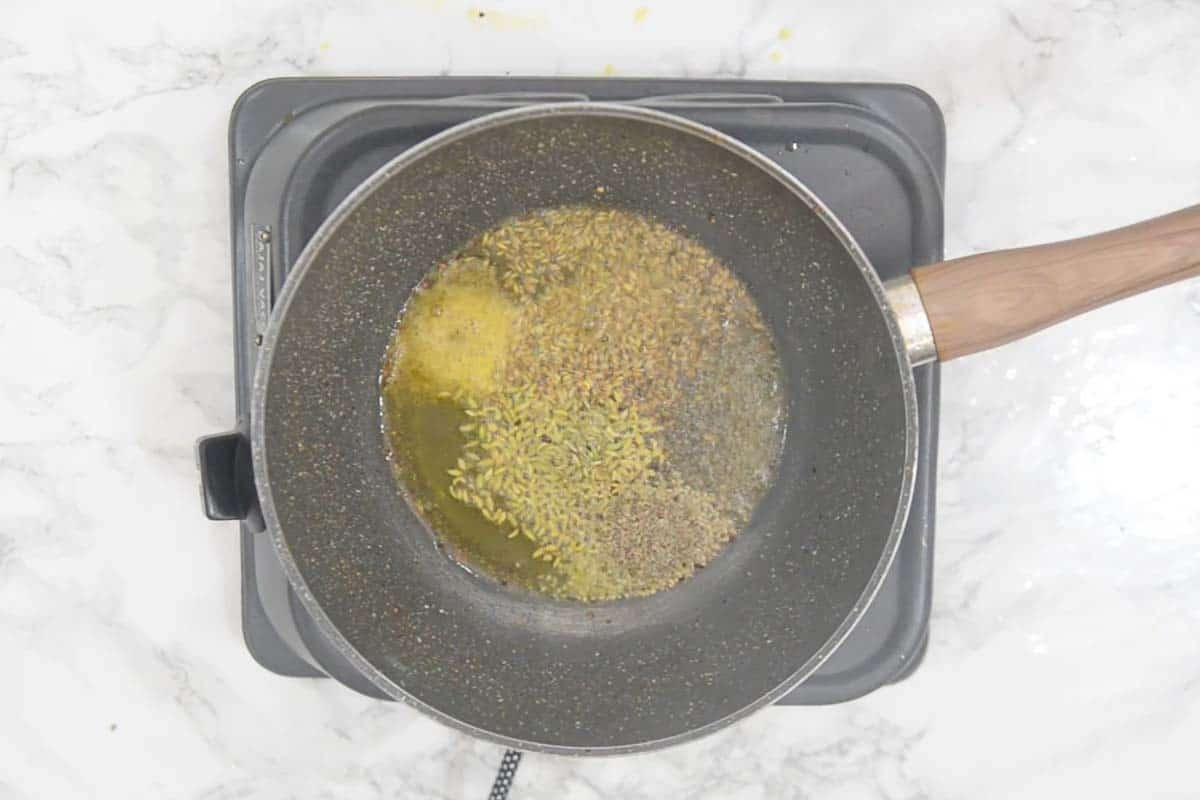 Mustard seeds, cumin seeds, hing, fennel seeds and carom seeds added in hot oil.