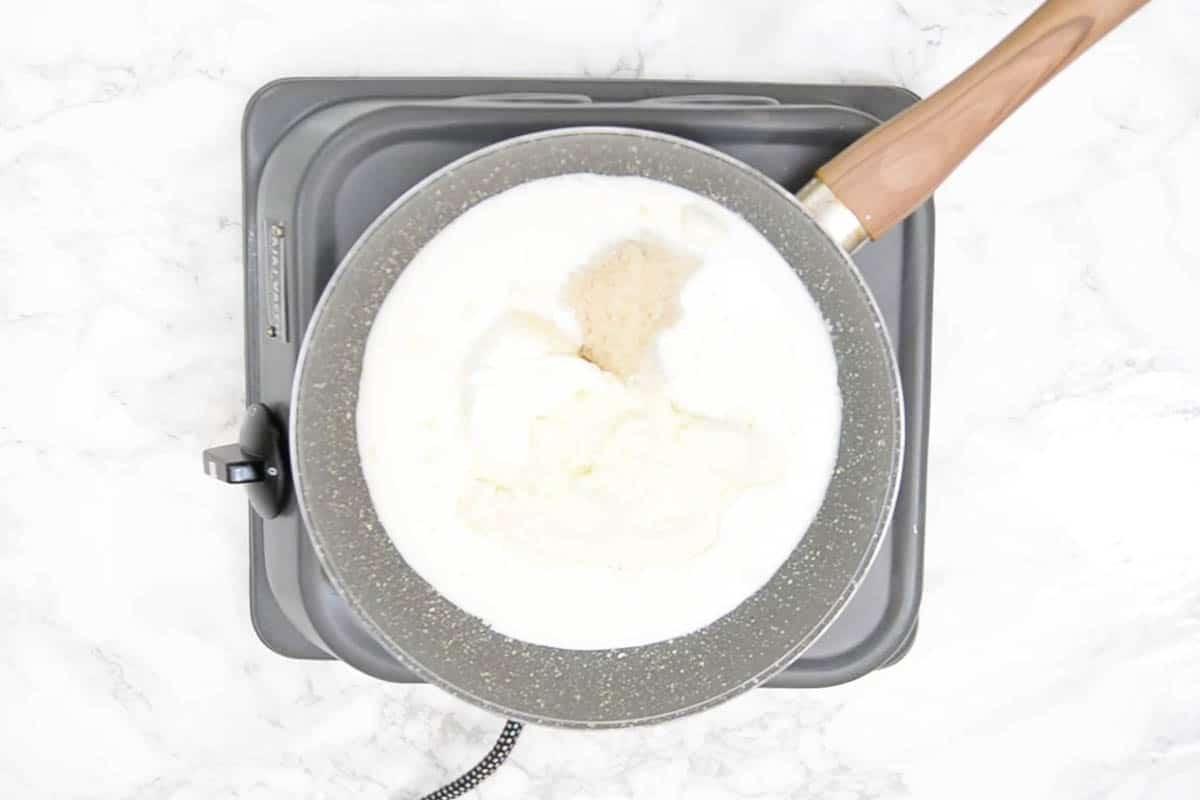 Ghee, milk powder, sugar, fresh cream, and milk heating in a pan.