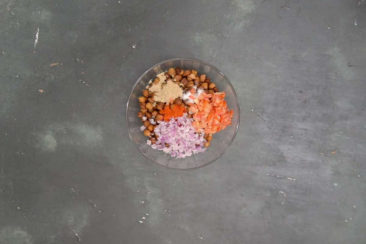Boiled kala chana, black salt, regular salt, chaat masala, red chili powder, onion, tomato, and lemon juice added in a bowl.