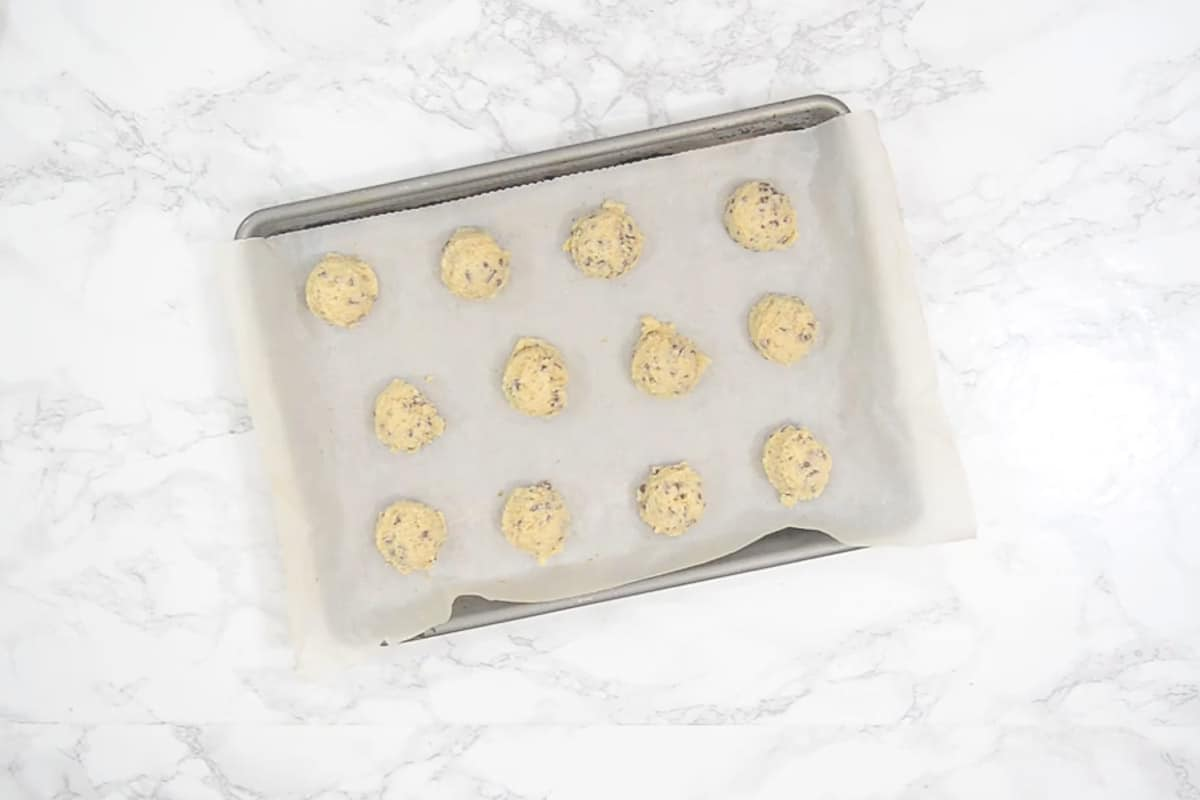 Cookies scooped on a tray lined with parchment.