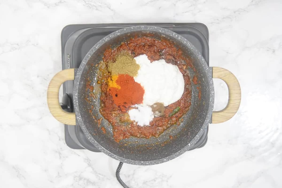 Yogurt, all purpose flour, coriander powder, turmeric powder, red chilli powder, garam masala powder and salt added in the pan.