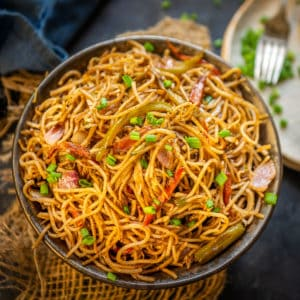 Hakka Noodles are easy and delicious wok-tossed noodles. Thin noodles are tossed with veggies and sauces on high flame to make this Chinese delicacy. Here is how to make it.