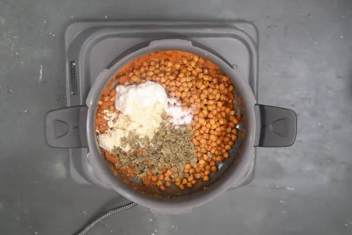 Soaked chana, yogurt, besan, kasuri methi, and salt added in the pan.