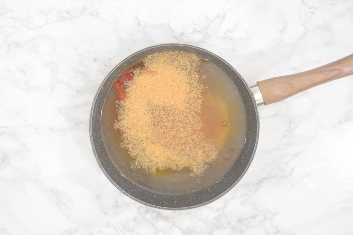 Salt, turmeric powder, red chili powder, and mustard powder added in the pan.