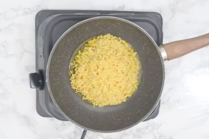 Drained dal added in a pan.