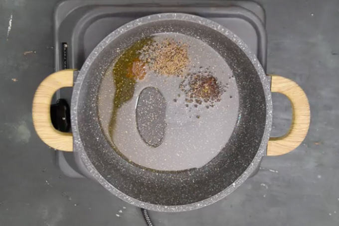 Hing, mustard seeds and cumin seeds added in hot oil.