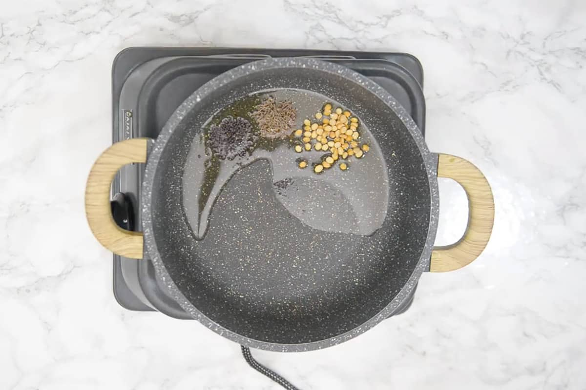 Mustard seeds, cumin seeds and chana dal added in hot oil.