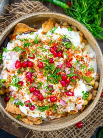 Samosa Chaat is a delicious Indian street food where crispy Punjabi Samosa is topped with a tangy and spicy chutney mixture. Here is how to make it.