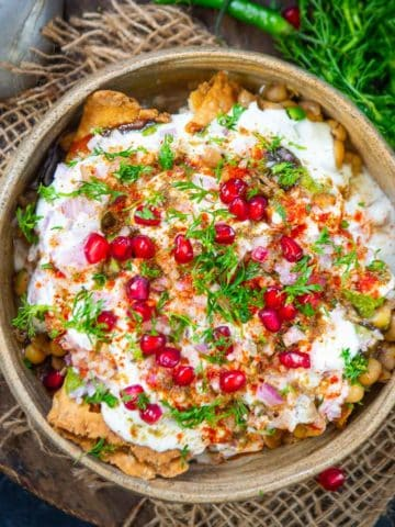 Tangy, Spicy, and Crispy, Samosa Chaat is a delicious Indian street food where crispy Punjabi Samosa is topped with yogurt and chutney mixture. Here is how to make it.