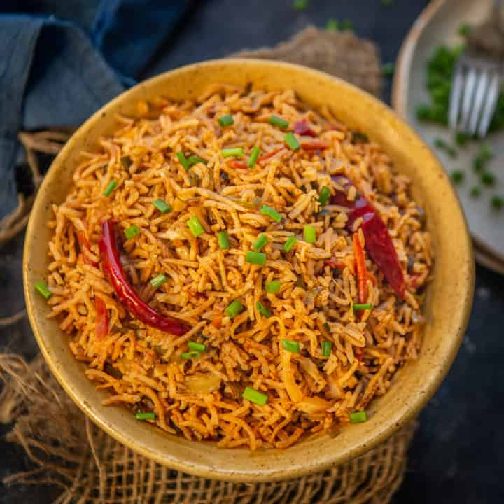 This spicy Schezwan Fried Rice is an easy and delicious rice stir fry dish where cooked rice is tossed with spicy sauces and veggies. Here is how to make it.