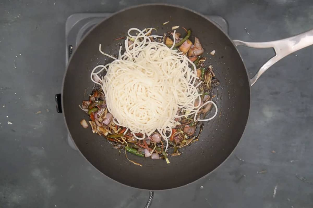Boiled noodles added in the wok.