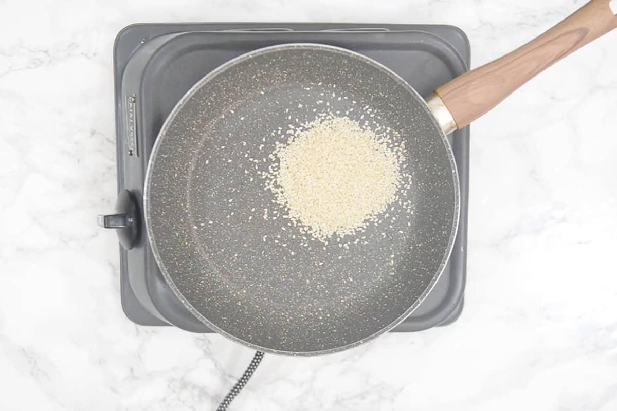 Sesame seeds roasting in a pan.