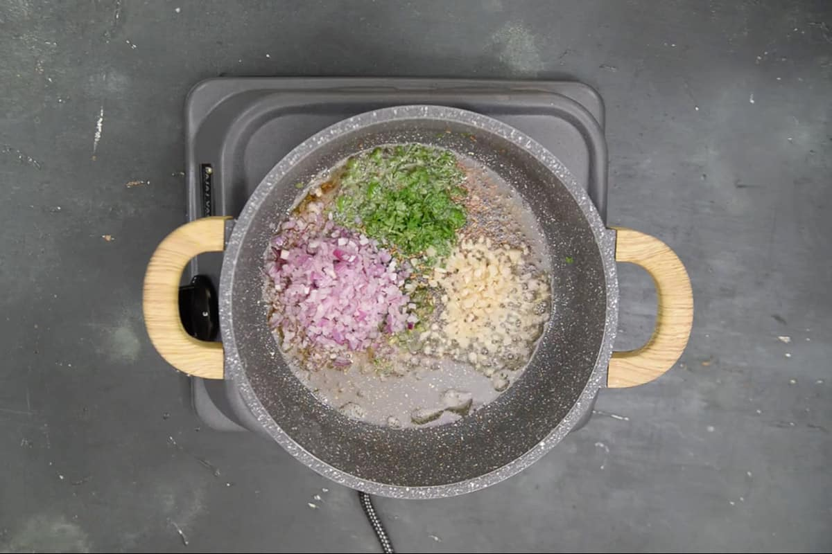Garlic, fresh coriander, green chilli and onion added in the pan.