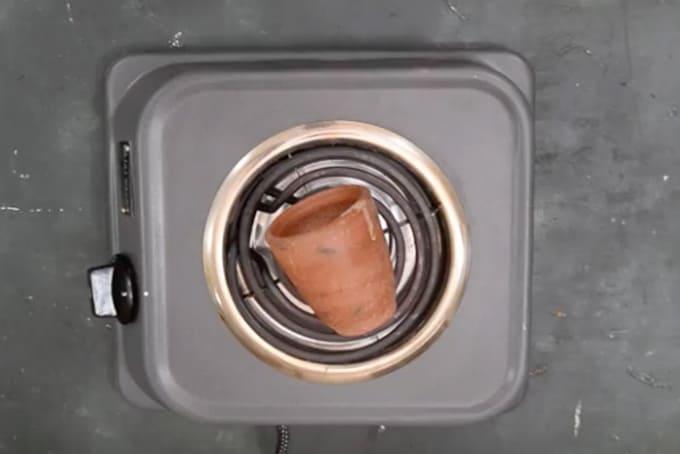 Clay mug heating on flame.