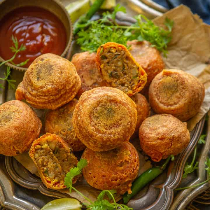 Aloo Bonda is an Indian snack where spicy potato filling is wrapped with a  crispy chickpea flour covering. This tea time snack is a favourite among people. Here is how to make it.