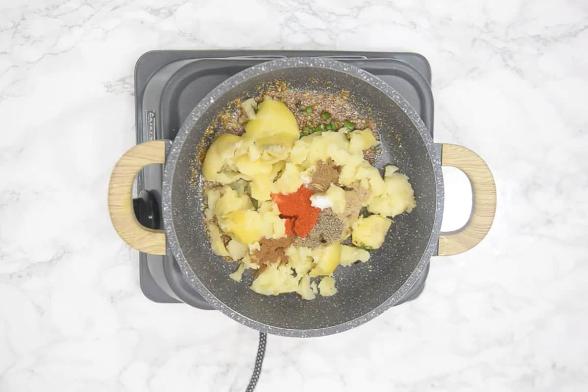 Potatoes and spices added in the pan.