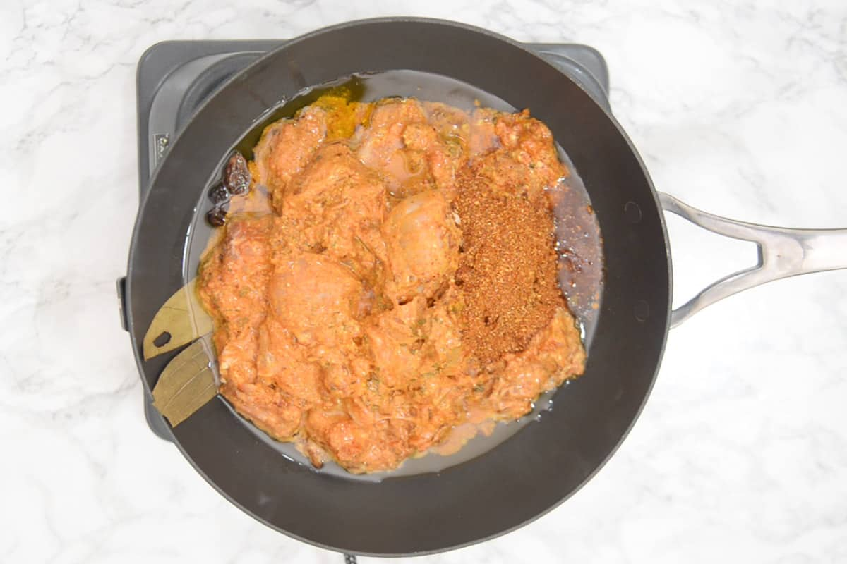 marinated chicken and ground masala added in the pan.