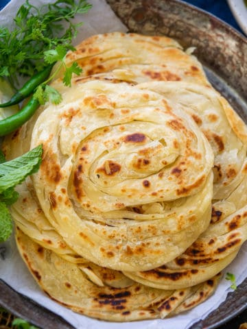 Kerala Parotta or Malabar Parotta is a layered Indian flatbread which goes great with curries. Here is how to make it in a traditional way.