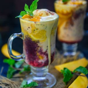 This super yummy Mango Falooda is an Indian beverage or dessert with layers of falooda sev, milk, basil seeds, and fresh mango pieces and mango puree layered in a tall glass. It is a delight to eat and one of the best mango recipes.