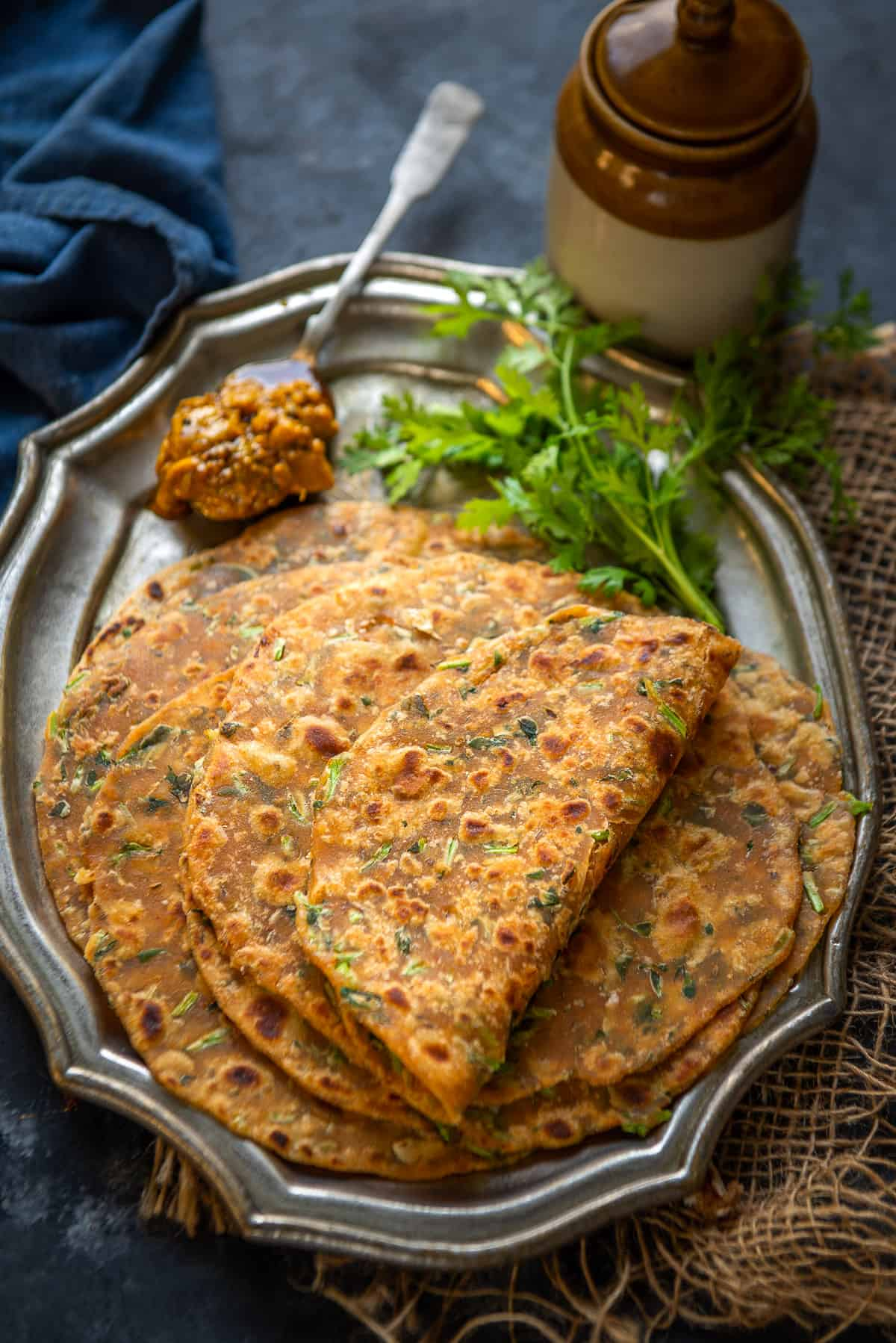 methi Paratha served on a plate with pickle.