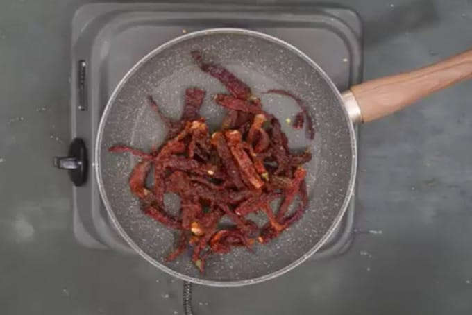 Chillies roasting in a pan.