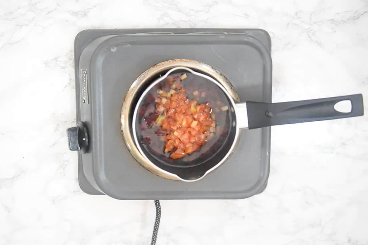 Beetroot and tomatoes cooking in a pan.