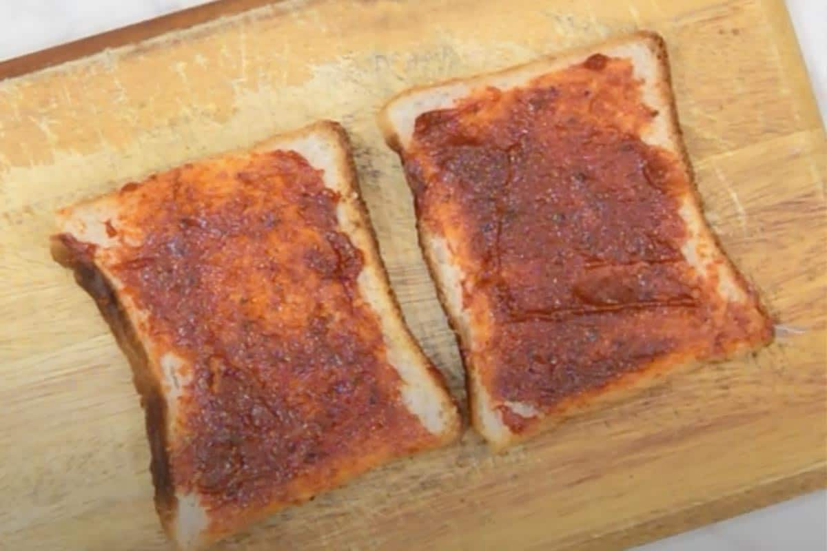 Pizza Sauce slathered on bread slices.