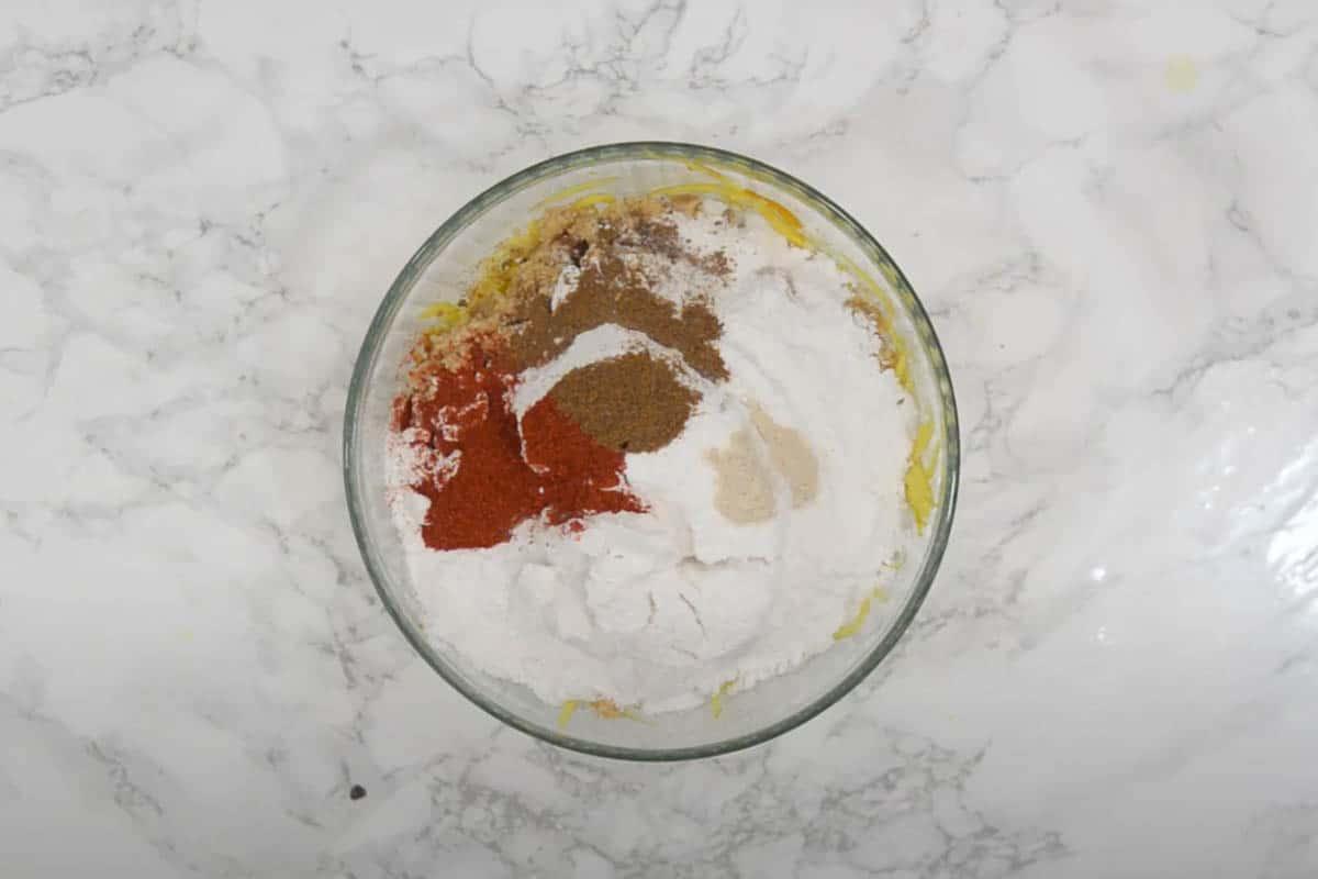 Jaggery, powdered sugar, asafoetida, Kashmiri red chili powder and ground cumin added to the bowl.