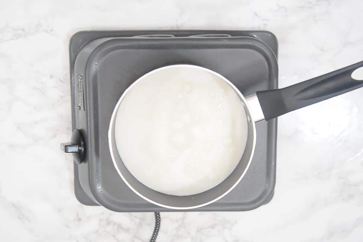 Milk and sugar heating in a pan.