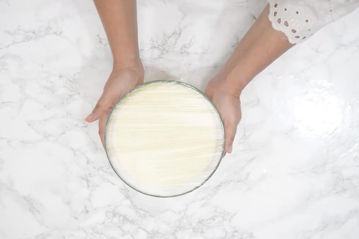Custard added in a bowl and covered with cling wrap.