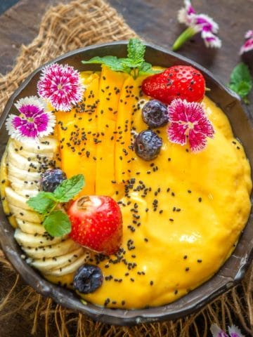 Start your day with this sweet tropical mango smoothie bowl which comes together in under 15 minutes. It's hearty and filling and can be made vegan and gluten-free.
