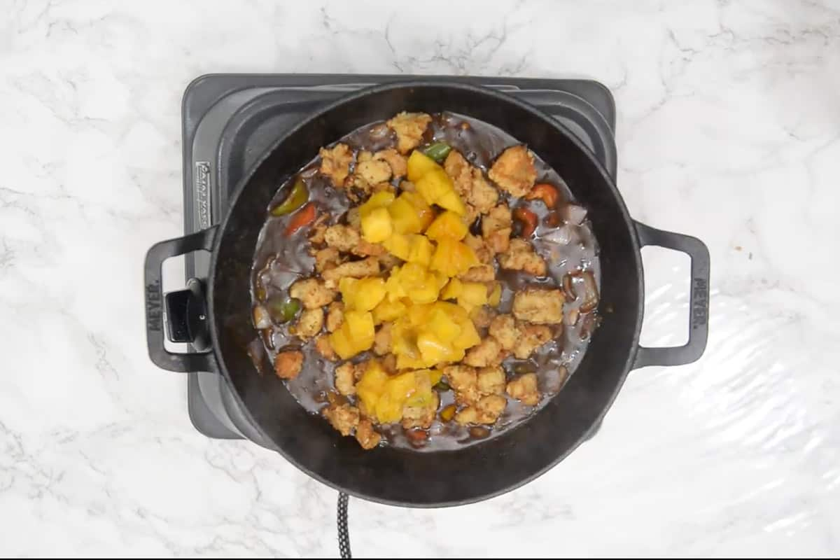 Fried chicken and mangoes added in the wok.