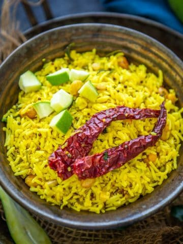 Raw Mango Rice, Mavinakayi Chitranna, or Mamidikaya Pulihora is South Indian green mango-flavored rice. This variety of rice is a lovely variation of the popular lemon rice but with a tang from green mangoes. Here is how to make it.