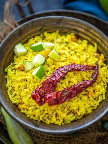 Raw Mango Rice, Mavinakayi Chitranna or mamidikaya Pulihora is South Indian green mango flavoured rice. This variety rice is lovely variation of the popular lemon rice but with a tang from green mangoes. Here is how to make it.