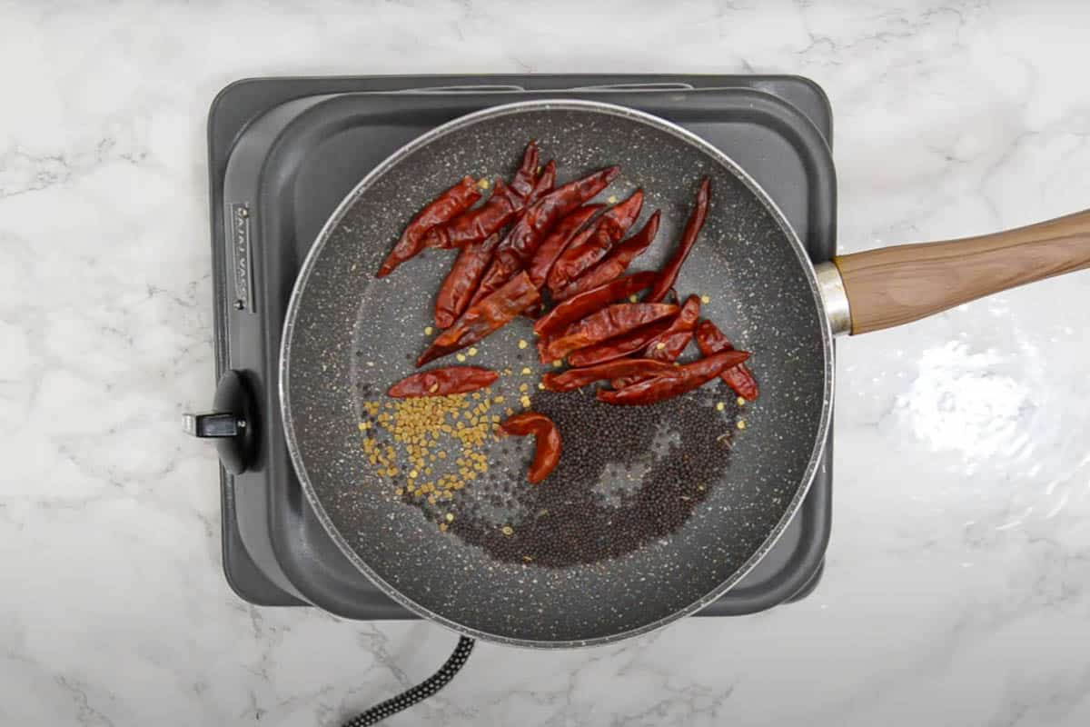 Dry red chilies, mustard seeds and fenugreek seeds roasting in a pan.