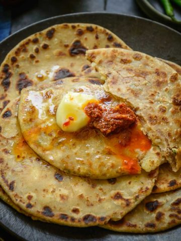 Aloo paratha is an Indian unleavened whole wheat flatbread stuffed with a spicy and super flavorful potato filling. It is one of the most popular breakfasts and is best enjoyed with plain yogurt, butter, and pickle. Check out my easy recipe with lots of variations, tips, and tricks.