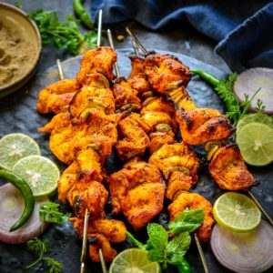 Tandoori Chicken Tikka or Murgh Tikka is a popular North Indian starter, where marinated chicken is grilled until perfection. This authentic snack recipe is great to make for parties or get-togethers and it comes together in under 10 minutes. Make it in an oven, stovetop, air fryer, or outdoor grill using my simple recipe.